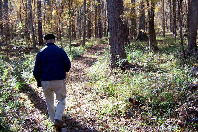 Image of a man hiking a trail at Angus Gholston.