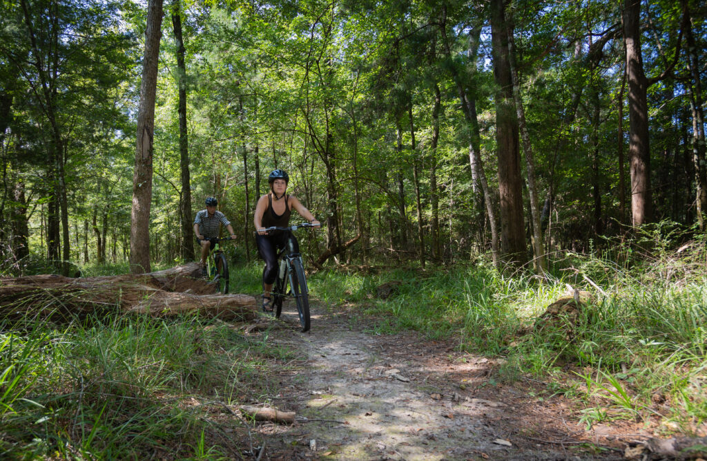 woman riding bike off-road through hinson conservation rec area