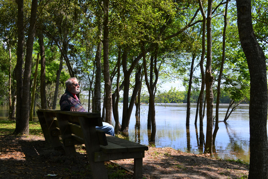 Image of man sitting on bench looking at river.