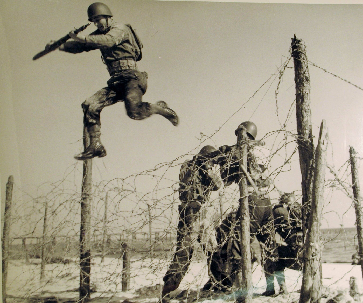Image of old war photo of military men jumping barbwire in Camp Gordon Johnston.