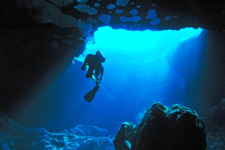 Image of a scuba diver cave diving at the mouth of the cave.