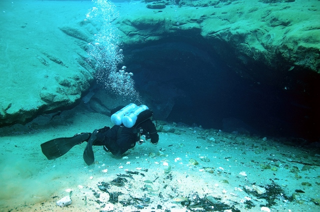 scuba diver at depth at the mouth of a spring head cave.
