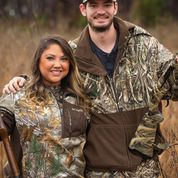 Two people standing side by side in hunting attire.
