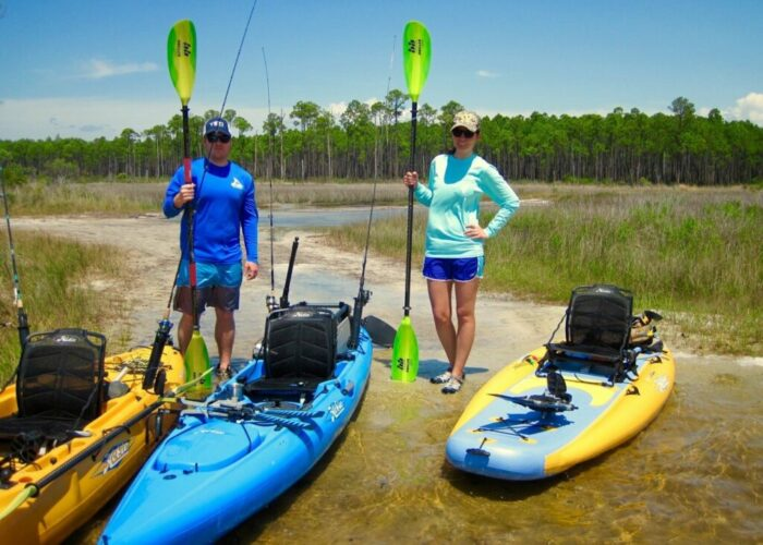 Image of two paddlers preparing to paddle out on the water.
