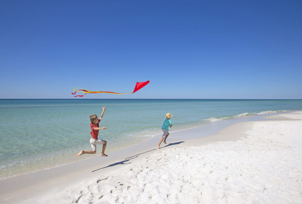 Image of two kids running on the beach with kites.