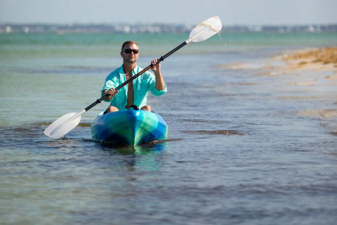 Image of a man paddling his kayak along the shoreline.