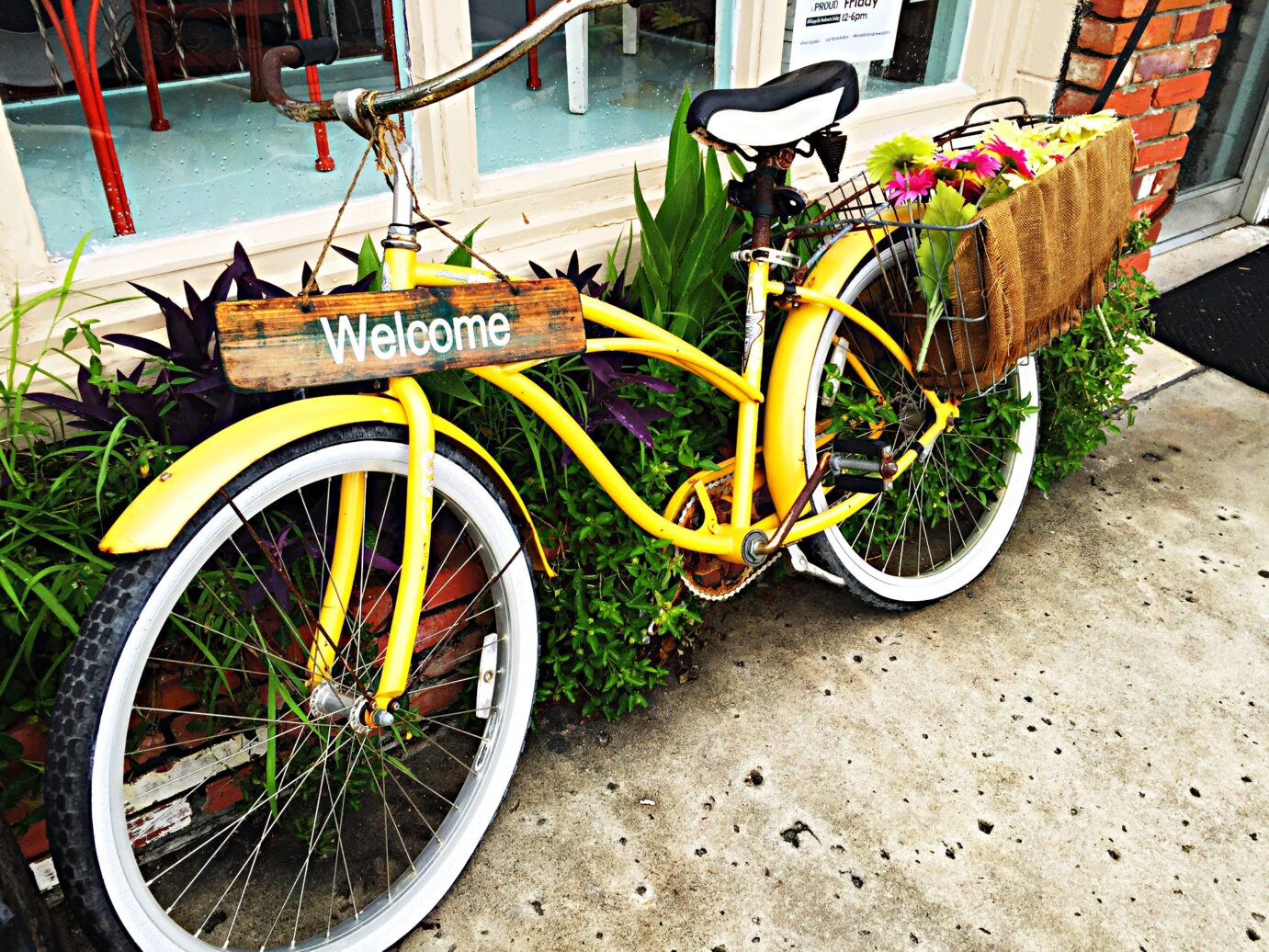 Image of welcome sign on a yellow bike with flowers.