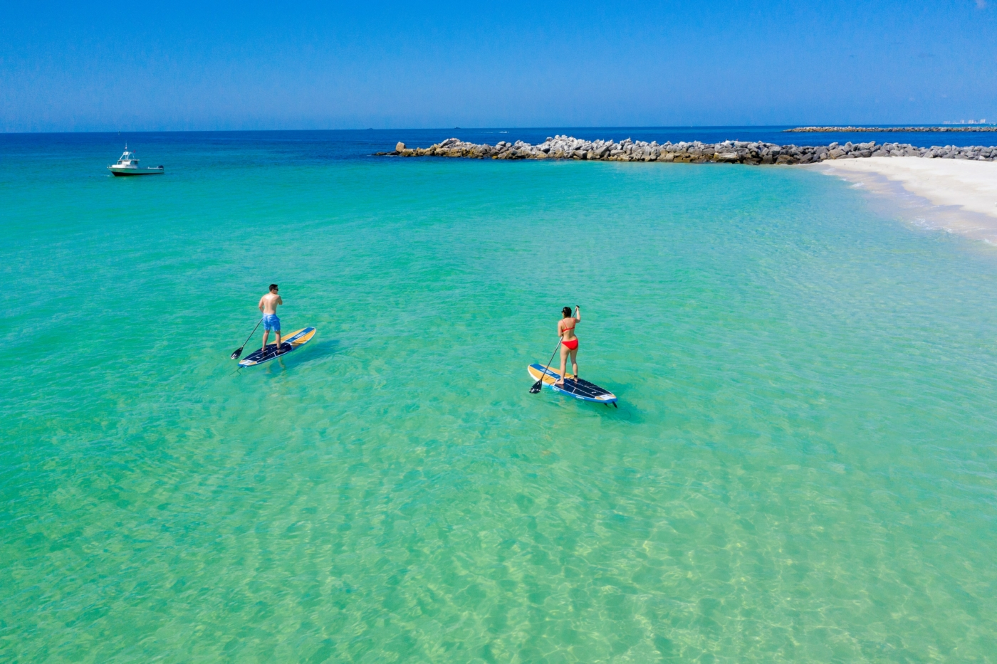 people paddling in the gulf near the jetties.