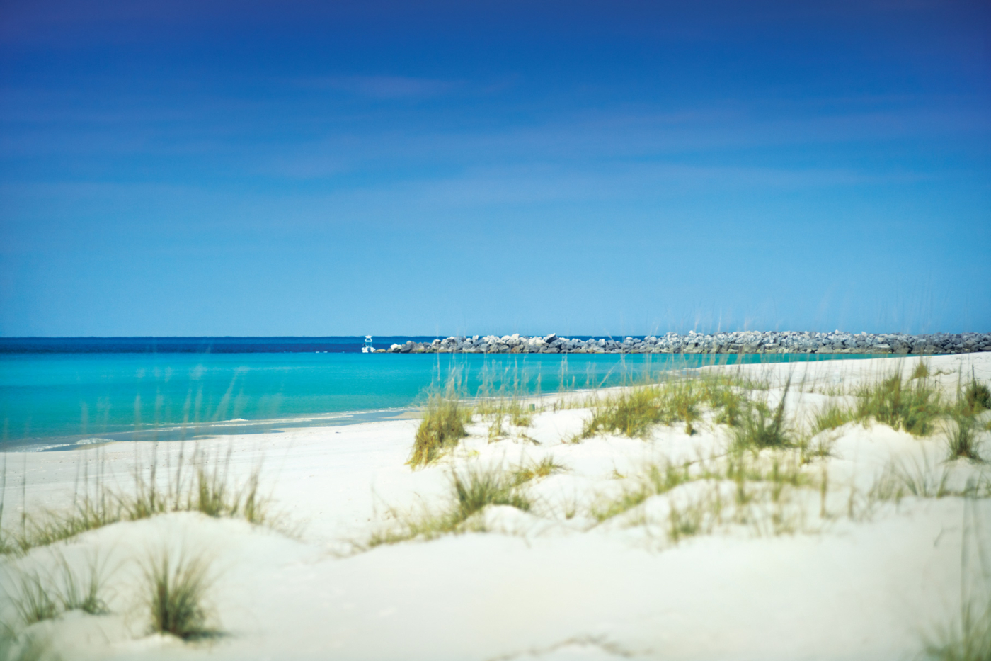 Image of emerald ocean water and white sand beach.