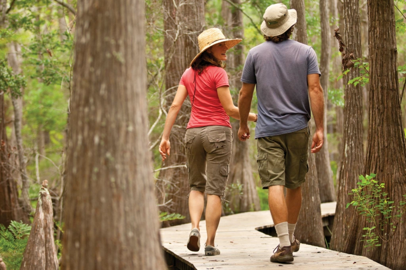Two people walking along a wood boardwalk at Point Washington State Park.