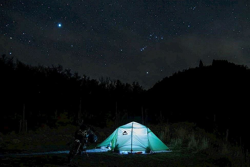 Image of a long exposure shot of a lit up tent camping in the middle of the night.