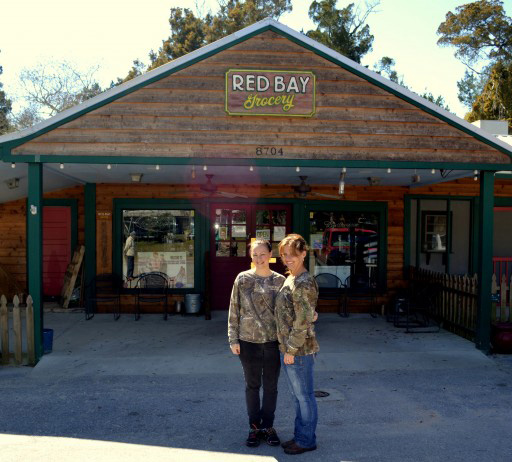 Image of people standing in front of the Red Bay Market.
