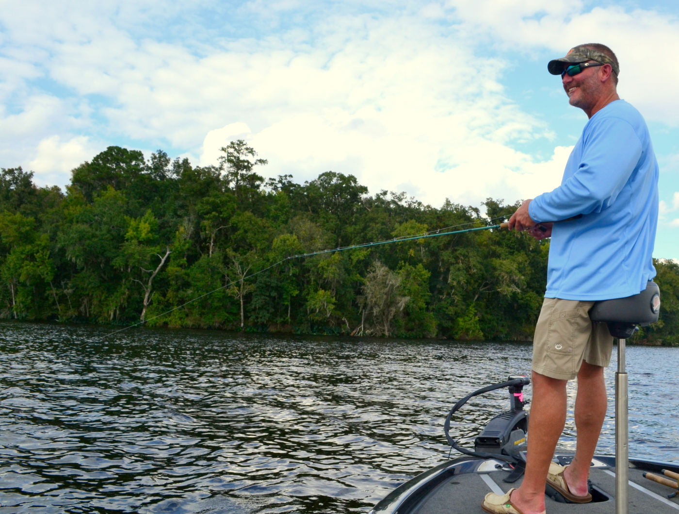 A man fishing on the bow of a bass boat.