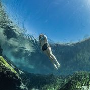 Image of a snorkeler surfacing from beneath the water