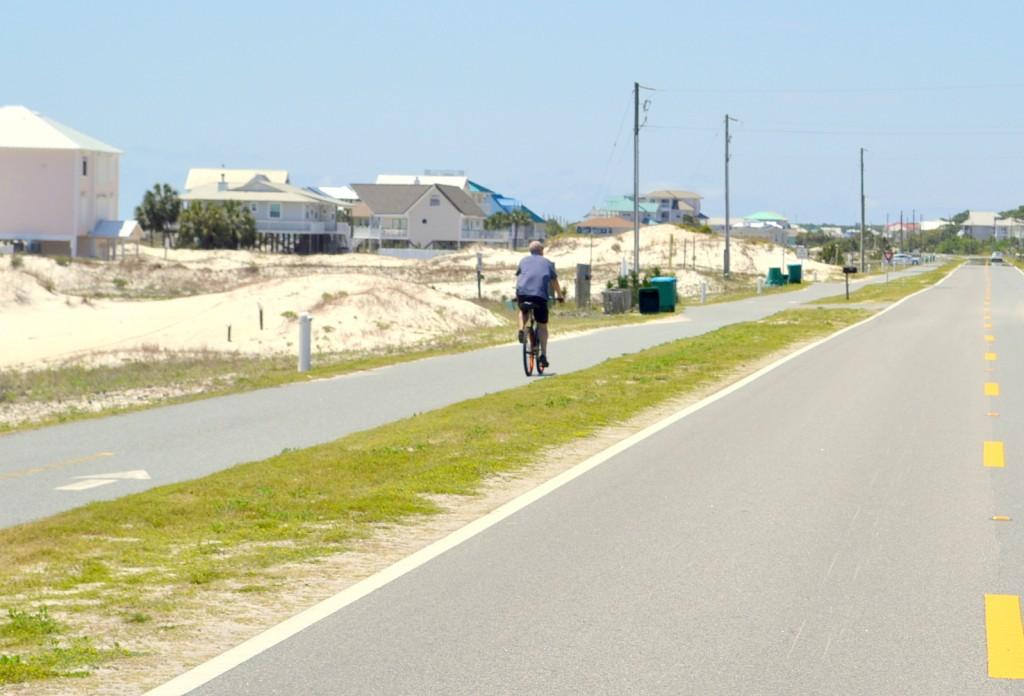 Image of someone biking down St. George Island sidewalk.