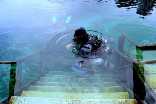 A scuba diver entering a spring.