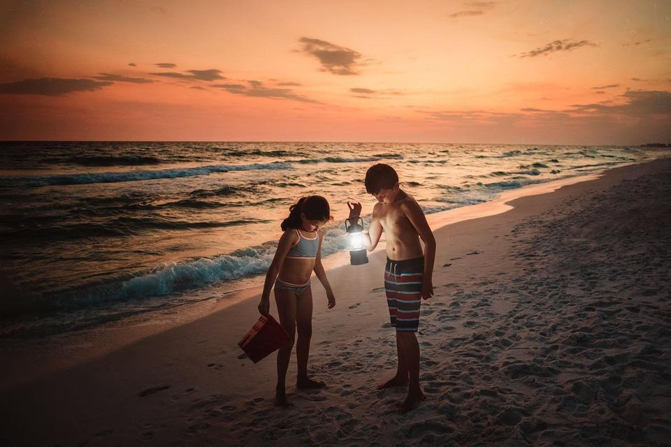 Image of two kids at sunset with a lantern playing in the sand.